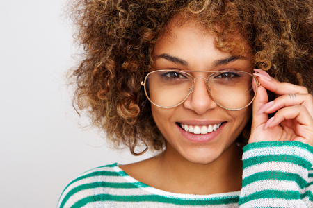 Close up portrait of beautiful young black woman smiling with glasses