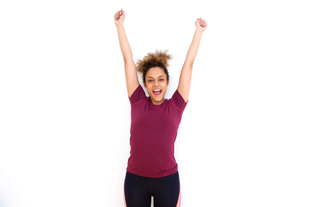 Portrait of cheerful young black woman smiling with arms raised against white background