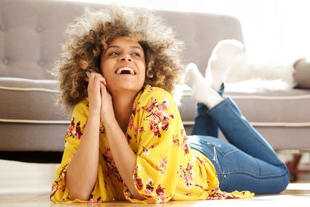 Portrait of attractive african american woman lying on floor at home and laughing