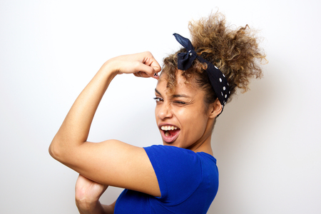 Close up portrait of cool young african american woman flexing bicep muscle