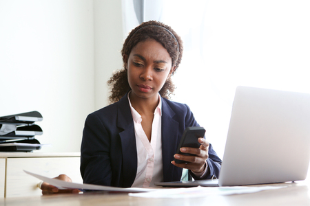 Portrait of young african business woman sitting at her desk and reviewing documents