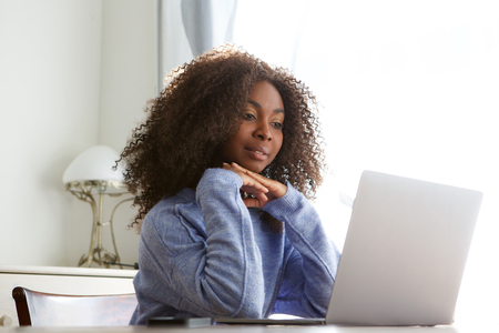 Portrait of young african woman sitting at table and looking at laptop screen