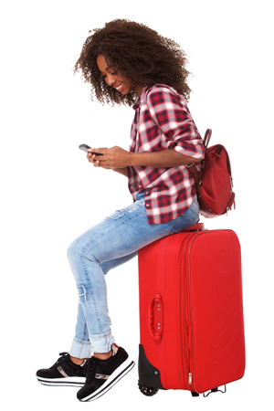 Full body portrait of young african woman sitting on suitcase and using mobile phone over white background