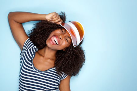 Close up portrait of happy young african american woman wearing cap on blue background
