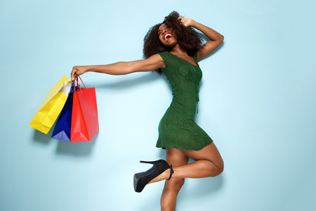 Portrait of excited young woman with shopping bags on blue background