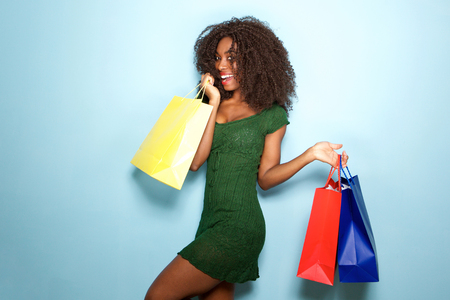 Portrait of beautiful african girl happy with shopping bags on blue background