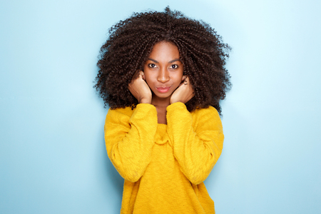 Portrait of beautiful young african woman holding ears  on blue background