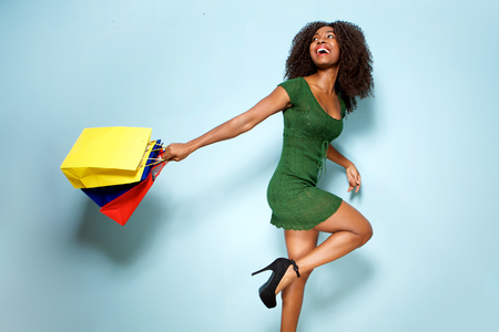 Portrait of happy young african american woman holding shopping bags on blue background Stock Photo
