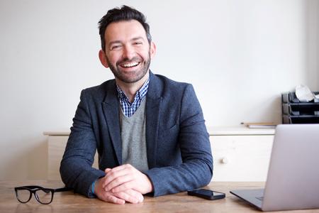 Portret van glimlachende zakenmanzitting in bureau