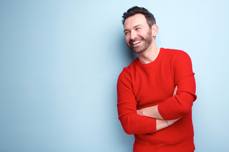 Portrait of cheerful man with beard laughing against blue background