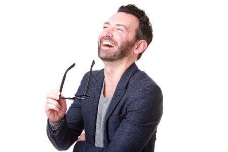 Portrait of man with beard holding glasses and laughing against white background Banco de Imagens
