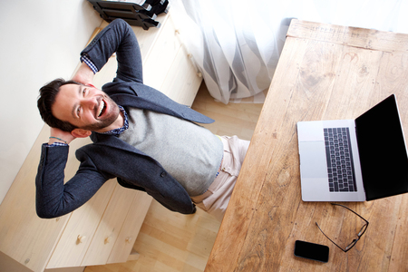 Portrait of happy businessman relaxing in office with laptop