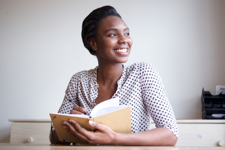 Portrait of smiling young black woman writing in journal at home