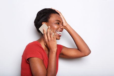 Close up side portrait of happy black woman talking on mobile phone and laughing