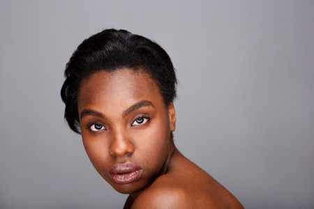Close up portrait of beautiful black woman with bare shoulders against gray background Foto de archivo