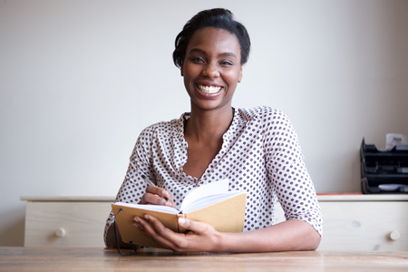 Portrait of smiling black woman at home writing in journal Stock fotó