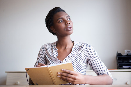 Portrait of serious young woman thinking and writing in journal
