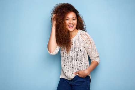 Portrait of happy young woman laughing with hand in hair Banque d'images - 103859308