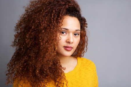 Close up portrait of beautiful young woman with curly hair against gray wall