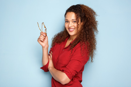 Portrait of happy african american woman with glasses against blue background Stock Photo - 103859950
