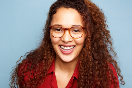 Close up portrait of young woman with glasses and curly hair smiling against blue background Banque d'images - 103926988