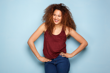Portrait of happy young woman with curly hair smiling against blue background Banque d'images - 103926996
