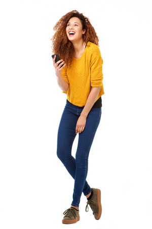 Full body portrait of happy woman with smart phone laughing against isolated white background