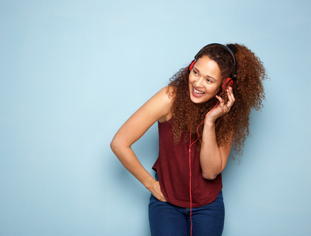 Portrait of young woman with curly hair listening to music with headphones