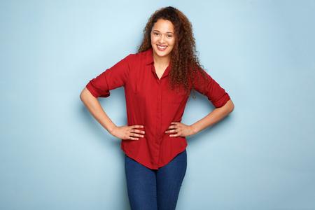Portrait of happy young woman smiling against blue background Banque d'images - 103927130