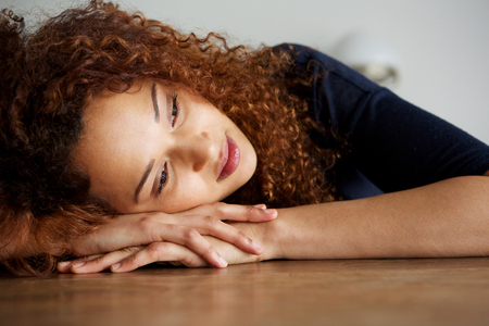 Close up portrait of tired young woman resting on table