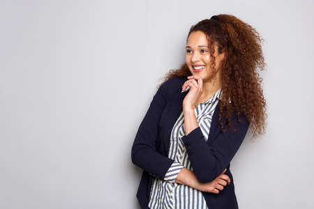 Portrait of attractive young businesswoman with curly hair smiling against gray background Banque d'images - 103927150