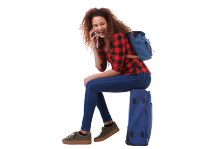 Full body side portrait of happy travel woman sitting on suitcase and talking on cellphone Foto de archivo