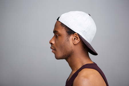 Close up profile portrait of african american man with cap on backwards