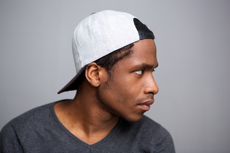 Close up side portrait of cool african american man with cap on backwards