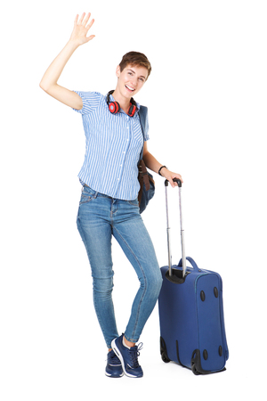 Full body portrait of happy young woman with travel bags waving her hand hello