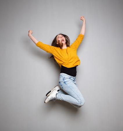 Actie portret van jonge vrouw springen in de lucht tegen een grijze achtergrond Stockfoto