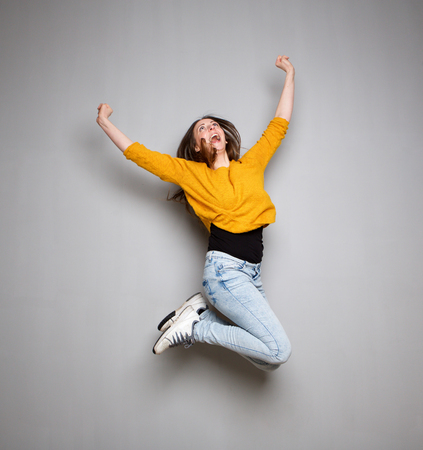 Retrato de acción de mujer joven saltando en el aire contra el fondo gris Foto de archivo