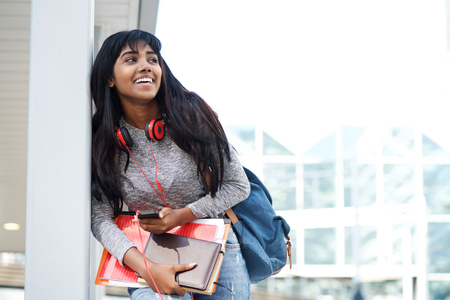 Portrait of smiling female student with mobile phone, books and bag