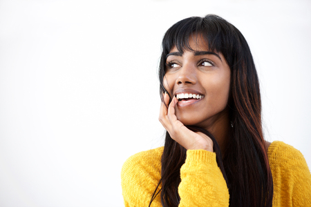 Close up portrait of smiling young Indian woman with hand by mouth