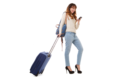 Full body portrait of smiling travel woman walking and looking at mobile phone