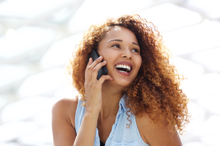 Close up portrait of happy young woman with curtly hair talking on mobile phone 스톡 콘텐츠
