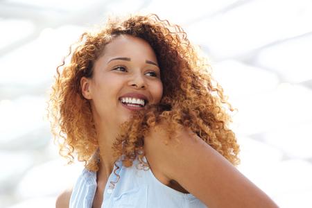 Bouchent le portrait de l'heureuse jeune femme aux cheveux sèchement regardant par-dessus l'épaule