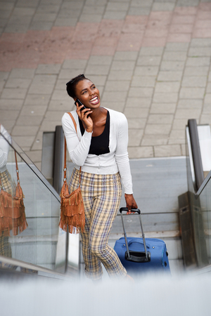 Portrait of happy african american woman standing on escalator with travel bags and  talking on cellphone Stock Photo