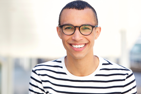 Close up portrait of happy young man with glasses