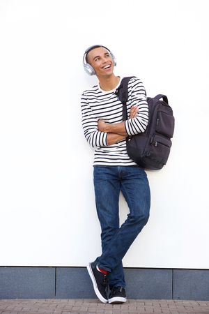 Full length portrait of happy young man leaning against white wall with bag and headphones Banque d'images - 113179228