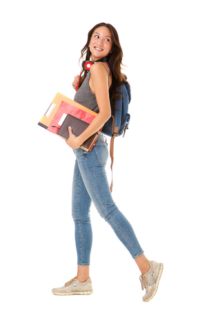 Full length portrait of smiling asian college student walking against isolated white background with books and bag 版權商用圖片 - 113179555