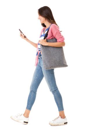 Retrato del lado del cuerpo completo de la mujer asiática joven de moda que camina con el bolso y el teléfono móvil contra el fondo blanco aislado