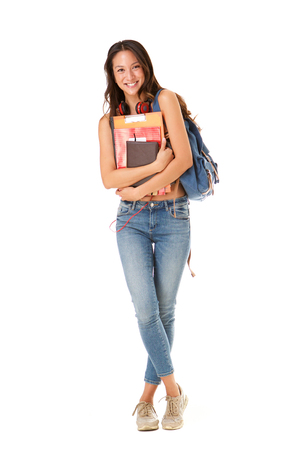 Full length portrait of smiling asian college student against isolated white background Foto de archivo