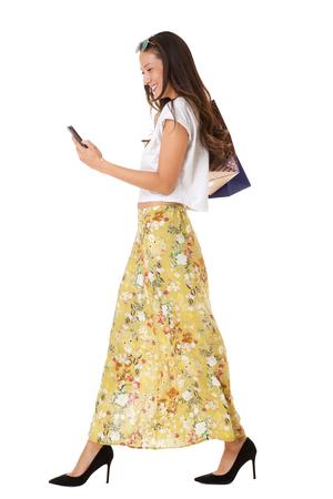 Retrato de cuerpo entero de mujer asiática sonriente caminando con teléfono móvil y bolsas de compras contra el fondo blanco aislado