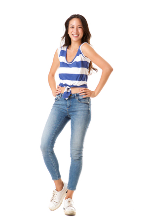 Full length portrait of stylish young asian woman posing against isolated white background with hands on hips